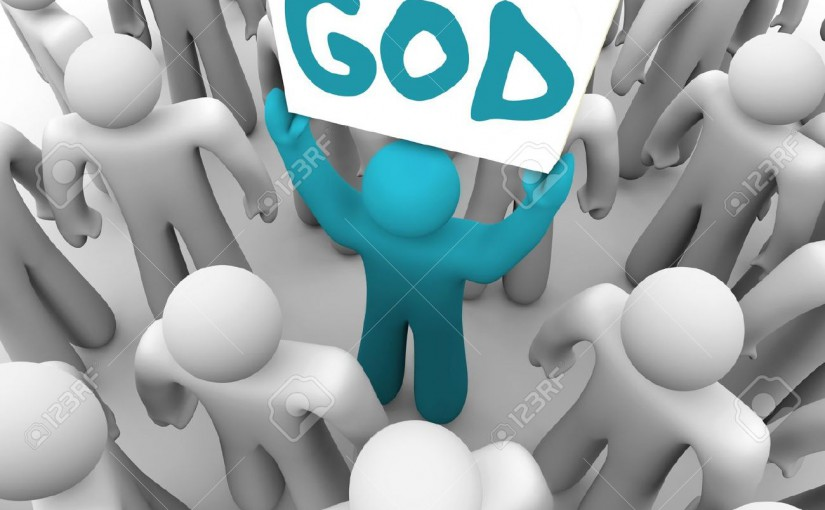 15565081-A-blue-person-stands-out-in-a-crowd-holding-a-sign-with-the-word-God-on-it-spreading-the-holy-teachi-Stock-Photo