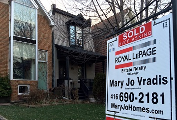 """A  """"sold over asking"""" sign sits in front of a detached house with an artificial grass front lawn, Toronto, Ont., Feb. 7, 2016. The home is located in the city's North Riverdale neighbourhood. THE CANADIAN PRESS IMAGES/Rachel Verbin"""