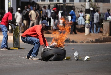 """Zimbabwe opposition supporters clash with police during a protest march for electoral reforms on August 26, 2016 in Harare. Riots erupted in Zimbabwe's capital Harare after police fired tear gas and beat protesters who responded by throwing stones in the latest of a string of tense demonstrations.  The violence came a day after a High Court judge had ordered police """"not to interfere (with), obstruct or stop the march"""". Dozens of police blocked off the site of an opposition rally to demand electoral reforms before 2018 when 92-year-old President Robert Mugabe, who has ruled the southern African country for decades, will seek re-election. / AFP PHOTO / WILFRED KAJESE"""