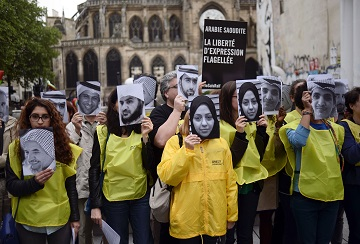 """People hold pictures of Samar Badawi (C) and her brotherb jailed Saudi blogger Raif Badawi (R) as they demonstrate in support of Raif Badawi, who was sentenced to 1,000 lashes for """"insulting Islam, on May 7, 2015 in Paris. The case of Badawi, 31, has sparked worldwide outrage and criticism from the United Nations, United States, the European Union, Canada and others.  Badawi co-founded with Suad al-Shammari the Saudi Liberal Network Internet discussion group. He was arrested in June 2012 under cybercrime provisions, and a judge ordered the website shut after it criticised Saudi Arabia's notorious religious police. Badawi was initially sentenced to seven years in jail and 600 lashes for insulting Islam and setting up the liberal network. AFP PHOTO / STEPHANE DE SAKUTIN / AFP / STEPHANE DE SAKUTIN        (Photo credit should read STEPHANE DE SAKUTIN/AFP/Getty Images)"""