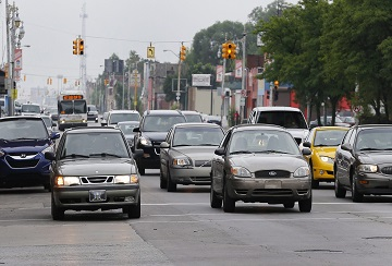 In this Thursday, July 9, 2015 photo, motorists drive on Grand River Boulevard in Detroit. It's called driving dirty and city officials estimate that one out of every two motorists living in Detroit is taking to the road without any type of auto insurance coverage. Data from CarInsurance.com shows the top 25 zip codes in the United States where drivers pay the most for car insurance are in Detroit, with some policies topping $5,000 annually. (AP Photo/Paul Sancya)