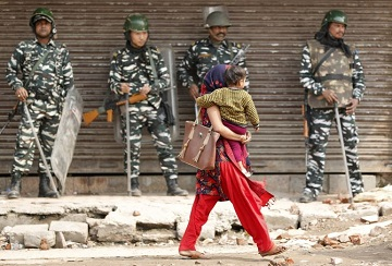 A woman carrying a child walks past security forces in a riot affected area after clashes erupted between people demonstrating for and against a new citizenship law in New Delhi, India, February 26, 2020. REUTERS/Adnan Abidi - RC2A8F9R2IP7